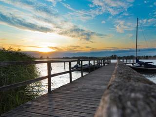 Sonnenuntergang mit Holzsteg und Booten an der Schlei in Schleswig-Holstein