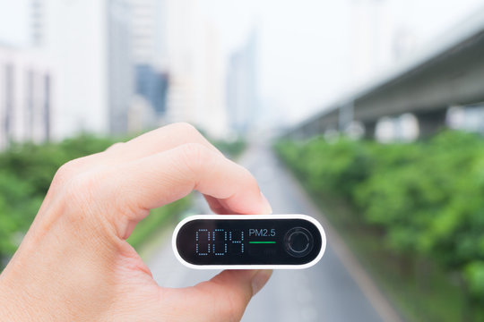 Closeup hand holding air quality monitor to detect level of pollution or small particulate (PM 2.5) in the city and it's show very low with green light, which mean air quality is good and safe. AQI.