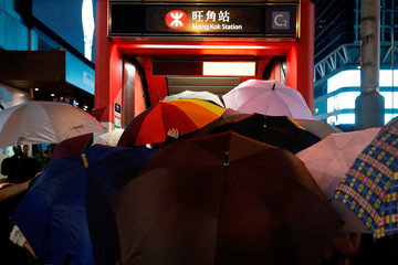 Anti-government protesters open umbrellas to block people to photograph during a demonstration after government's ban on face masks under emergency law, at Mong Kok, in Hong Kong