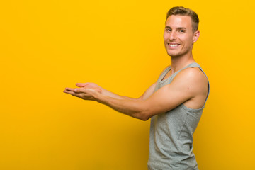 Young caucasian sport man holding a copy space on a palm.