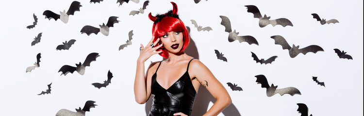 panoramic shot of girl in devil Halloween costume near white wall with decorative bats