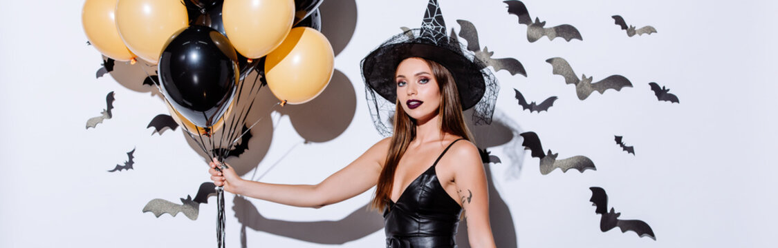 panoramic shot of girl in black witch Halloween costume holding balloons near white wall with decorative bats