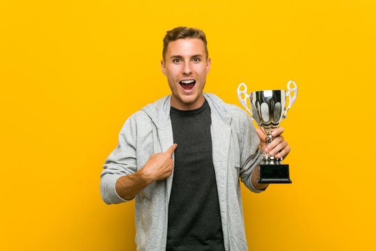 Young caucasian man holding a trophy surprised pointing at himself, smiling broadly.