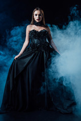scary vampire girl in black gothic dress on black background with smoke