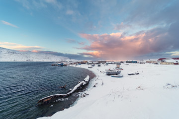 View of the old Russian fishing village of Teriberka with a shipwreck at the mouth of the namesake river on the Barents Sea, well above the Arctic circle in the Kola Peninsula near Murmansk