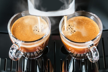 freshly brewed coffee is poured from the coffee machine into glass cups