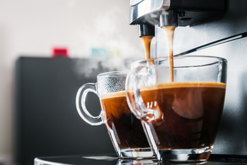 Papiers peints Cafe freshly brewed coffee is poured from the coffee machine into glass cups in the kitchen at home