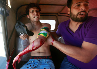 A man is seen assisting an injured demonstrator at a protest during a curfew, three days after the nationwide anti-government protests turned violent, in Baghdad