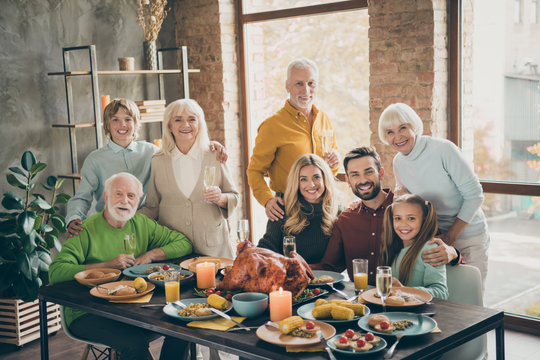 Photo of big family standing hugging feast table holiday roasted beef turkey making portrait eight members relatives multi-generation raising wine glasses in living room indoors