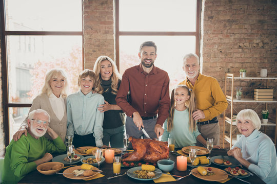 Photo of big family standing hugging feast table holiday roasted turkey making traditional portrait eight relatives multi-generation evening in living room indoors