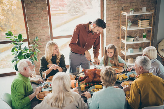 Photo of big family sit feast meals table around roasted turkey father guy making slice for little daughter hungry relatives evening party in living room indoors