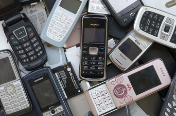 Bunch of old used outdated mobile phones and batteries. Recycling electronics