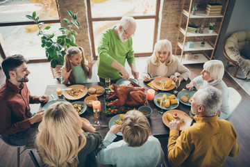 Photo of big family sit feast dishes table around roasted turkey eldest grandfather making slices hungry relatives waiting excited in living room indoors