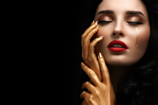 Close-up portrait of beautiful young woman with bright red lipstick and golden hands and tears