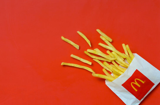 McDonald's French fries in small paperbag on bright red background