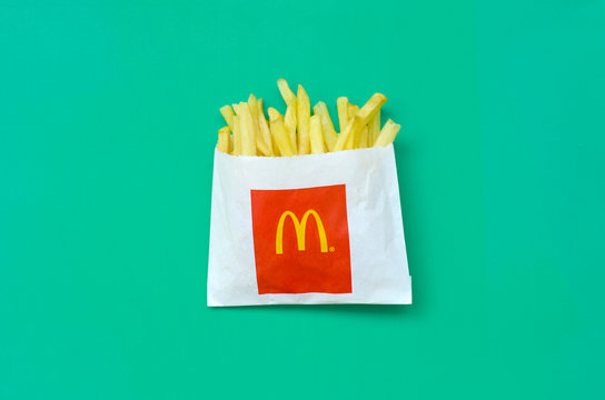 McDonald's French fries in small paperbag on bright green background