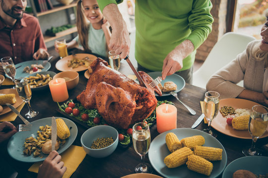 Cropped photo of full family sit feast dishes table around roasted turkey grandfather cutting meat into slices hungry relatives waiting excited in living room indoors