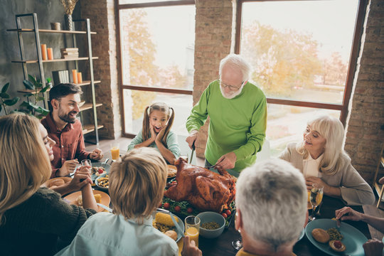 Let's pray. Photo of big family sit feast dishes table around roasted turkey grandfather making slices hungry relatives waiting excited in living room indoors