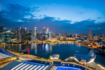 Aerial view of Singapore business district skyline with tourist sightseeing in night at Marina Bay, Singapore. Asian tourism, modern city life, or business finance and economy concept
