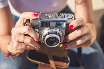 Woman's hands holding an old analog photography camera