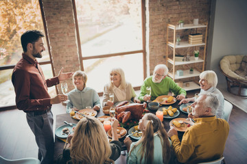 Photo of full big family gathering sit feast meals dinner table father guy telling thanksgiving pray toast multi-generation harmony in evening living room indoors