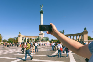 Man with phone in his hand taking picture of Heroes' Square (Hosok tere), major square and tourist attraction in Budapest, Hungary