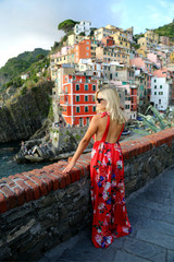 Fotobehang Liguria Blond girl traveller in a long red dress enjoying the view of Cinque Terra Liguria Italy. Freedom concept. Luxury lifestyle.
