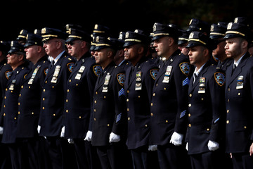Officers stand at attention as hearse carries the casket of shot New York City Police Department (NYPD) officer Brian Mulkeen to his funeral service at Sacred Heart Church in Monroe