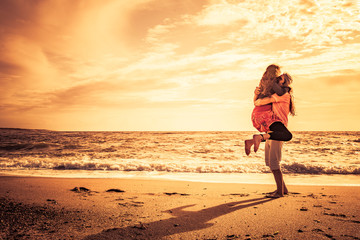 Fotoväggar - Glückliches Paar am Strand bei sonnenuntergang