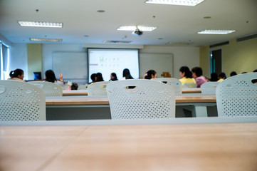 Selective focus on row of empty chairs with blurred group of students in background