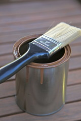 Farbdose auf einer Holzterrasse mit Pinsel