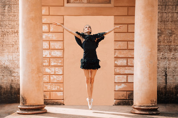 Young ballerina posing with a black dress