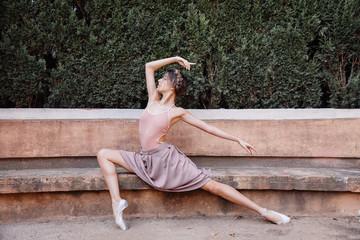 Young ballerina posing outdoors