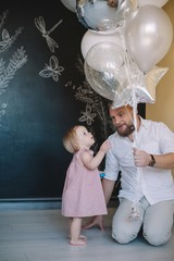 Father giving balloons for his baby girl
