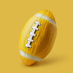 Melon in the form of an American football ball on a yellow backg