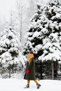 Anonymous woman walking in winter forest