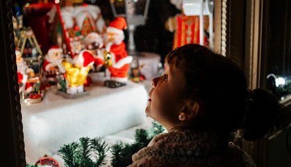 Little girl looking at a Christmas showcase