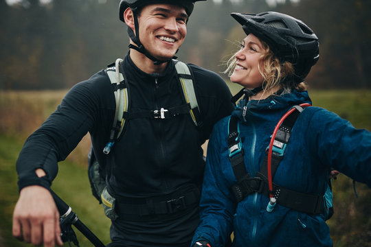 Smiling friends about to go for a mountain bike ride