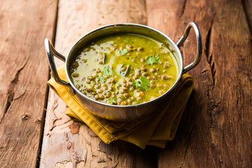 Black Masoor Dal fry or Dhaba Style Sabut Red Lentil dhal tadka in green curry, served in a bowl. selective focus Wall mural