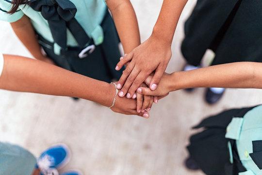 Unrecognizable children putting hands in stack