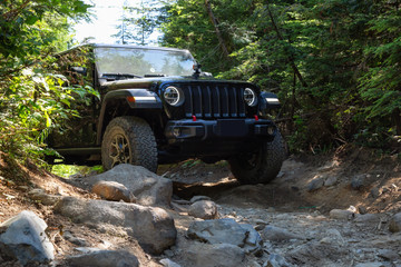 Mission, British Columbia, Canada - August 6, 2018: Jeep Rubicon is riding thru rough and rugged terrain to the lake.