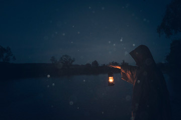 Man with lantern on the shore