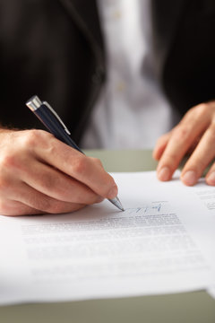 Closeup of man signing paper