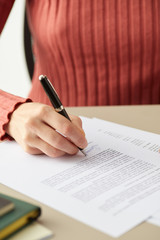 Woman signing?contract with pen