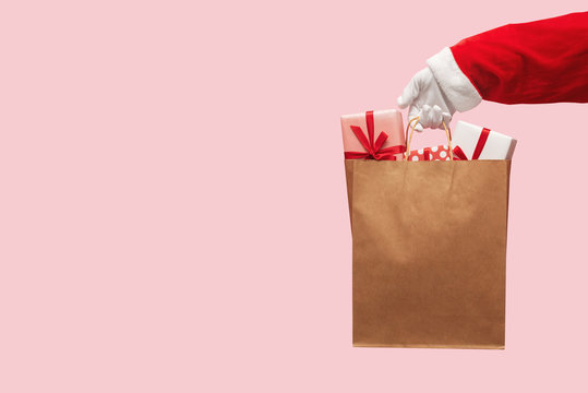 Santa Claus hand holding brown shopping bag with gift boxes