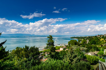 Photo sur Aluminium Bleu nuit Top view of the green coast and the port of Thonon les Bains, boats, Lake Geneva, and the blue sky with clouds.