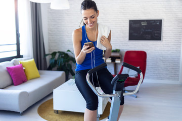 Smiling fitness girl using mobile phone after training on exercise bike at home.