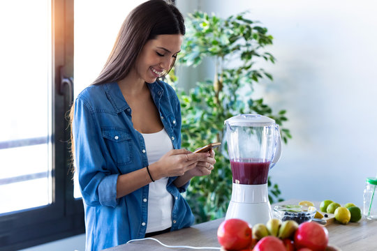Pretty young woman using her mobile phone while preparing fruit smoothie in the kitchen at home.