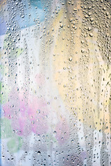 Drops of water flow down the surface of a transparent glass on an abstract blurred bright colored background.