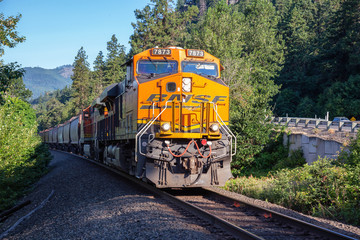 White Salmon, Washington, United States - June 30, 2019: Commercial Train riding in Columbia River during a sunny summer morning.